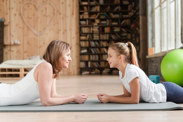 Mother and daughter sitting on mat looking at each other