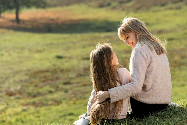 Mother and daughter sitting in nature