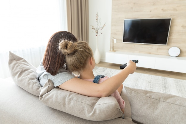Mother and daughter sitting on sofa watching tv