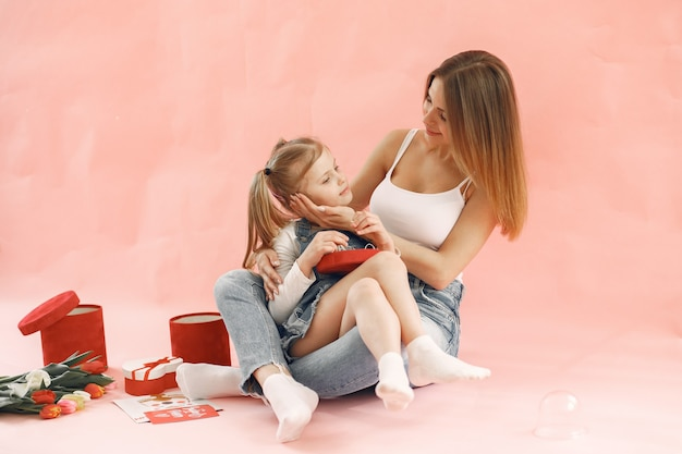 Mother and daughter sitting together. pink wall. mother's day concept.