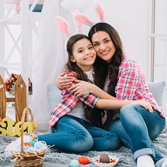 Mother and daughter sitting with easter eggs on bed embracing each other