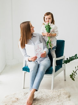 Mother and daughter sitting with greeting card