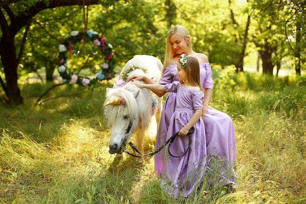Mother and daughter sitting in the woods with a white pony.