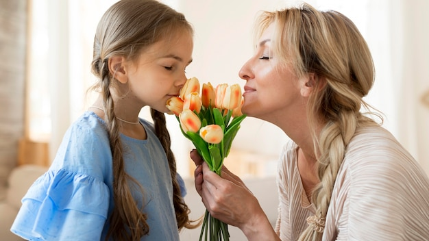 Mother and daughter smelling bouquet of tulips