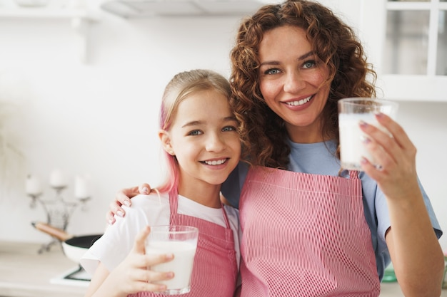 Mother and daughter smiling and holding glasses of milk in kitchen
