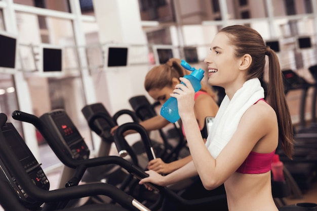 Mother and daughter in sportswear drinking water in gym