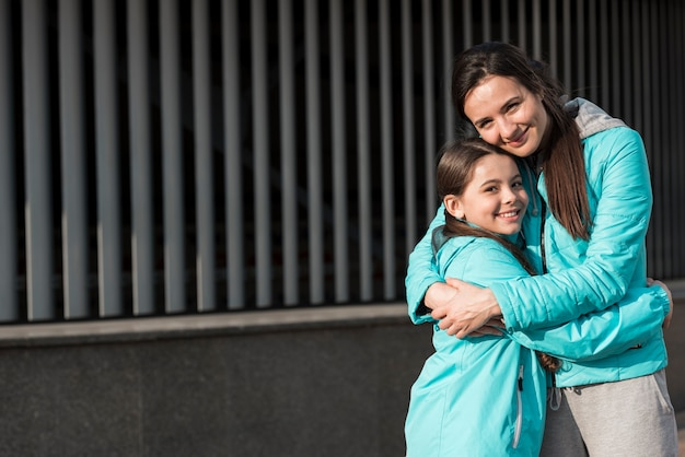 Mother and daughter in sportswear hugging with copy space