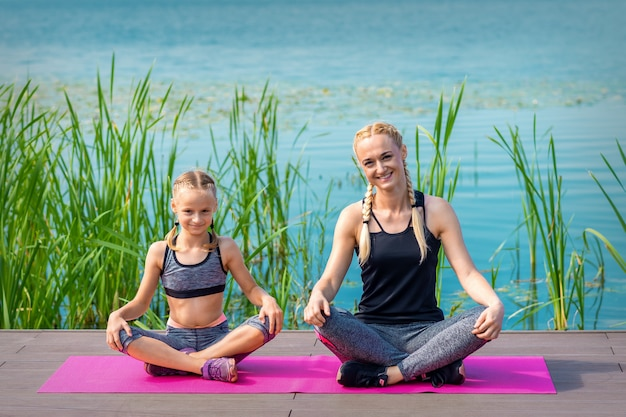 Mother and daughter in sportswear sitting on the mat on the pier near the water outdoor