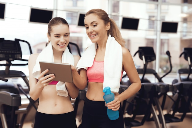 Mother and daughter in sportswear using tablet at the gym