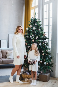 Mother and daughter stand near the christmas tree, decorate the christmas tree, light hair and white sweaters, beautiful decorations, holiday mood