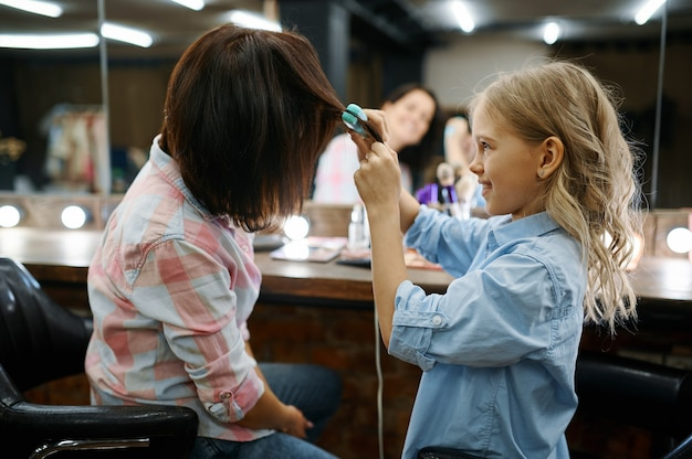 Mother and daughter straighten their hairstyles in hair salon