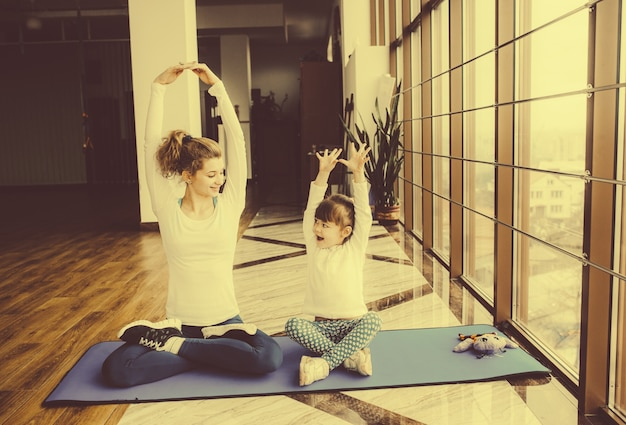 Mother and daughter stretching arms