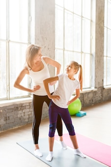 Mother and daughter stretching in gym