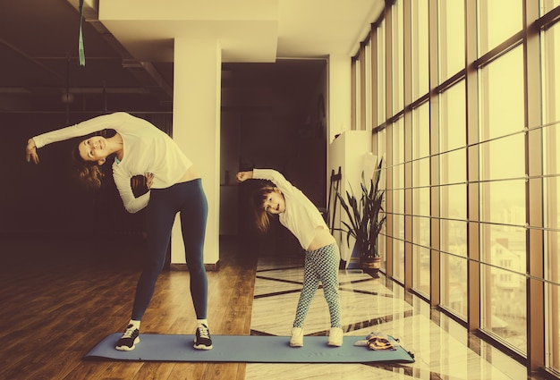 Mother and daughter stretching together