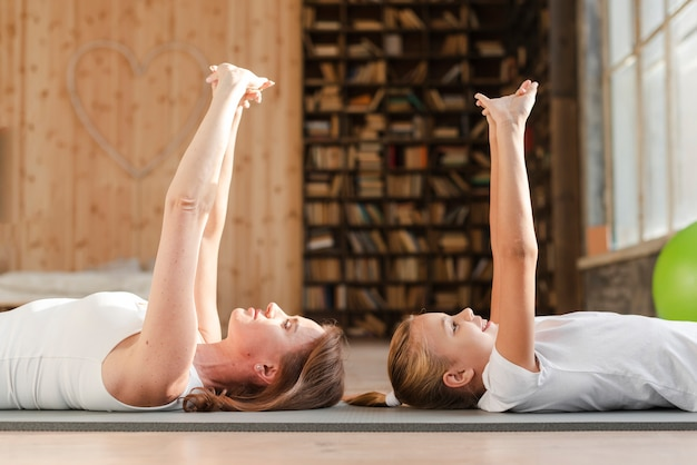 Mother and daughter stretching on yoga mat