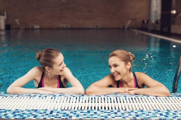 Mother and daughter in swimsuits at border of pool at gym.