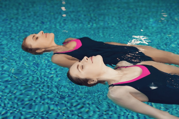 Mother and daughter in swimsuits swimming in pool at gym.