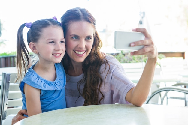 Mother and daughter taking selfie at cafe terrace