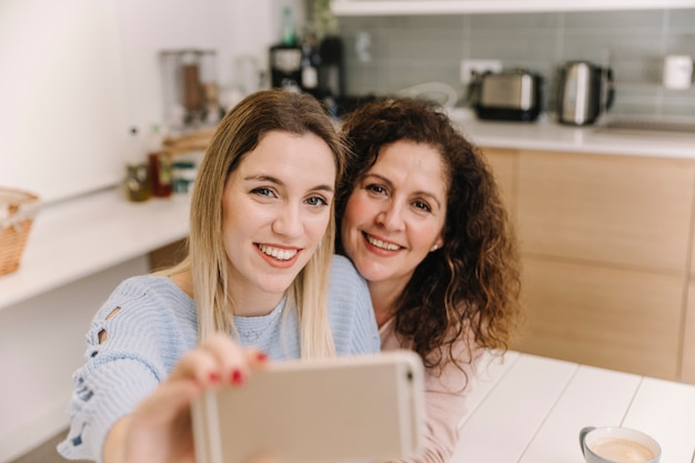 Mother and daughter taking selfie in kitchen