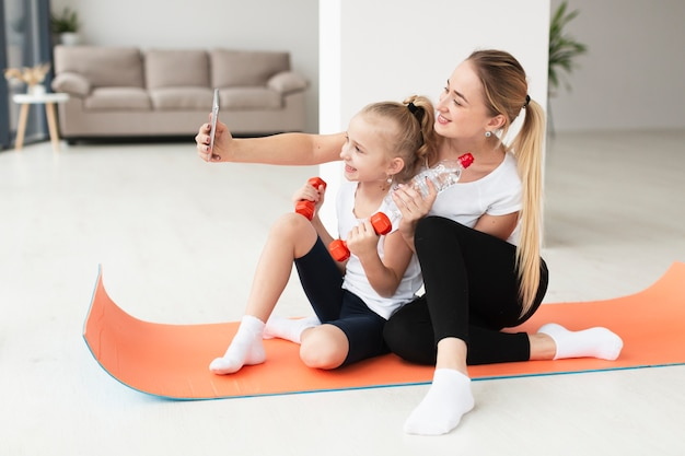 Mother and daughter taking selfie while holding weights