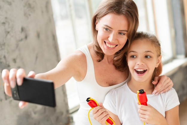 Mother and daughter taking selfie with jump rope