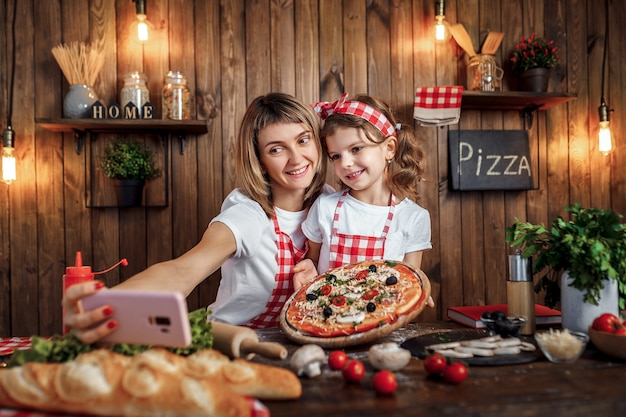 Mother and daughter taking selfie with pizza on smartphone