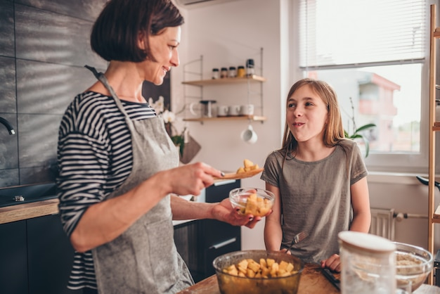 Mother and daughter tasting apple pie filling