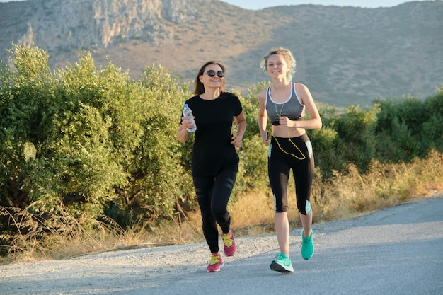 Mother and daughter teenager running outdoor on road in mountains on summer sunny day