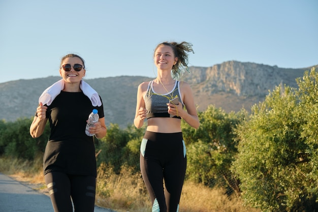 Mother and daughter teenager running outdoor on road in mountains