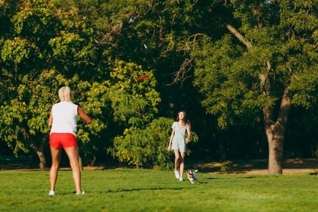 Madre e figlia che lanciano il disco volante arancione al piccolo cane divertente, che lo cattura sull'erba verde. piccolo animale domestico di jack russel terrier che gioca all'aperto nel parco. cane e donne. famiglia che riposa all'aria aperta