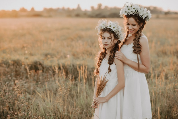 Mother and daughter together in white dresses with braids and floral wreaths in boho style in the summer field at sunset