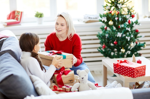 Mother and daughter unwrapping christmas presents