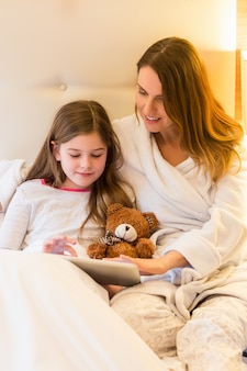Mother and daughter using digital tablet in bedroom