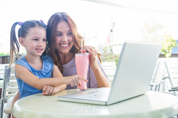 Mother and daughter using laptop at cafe terrace