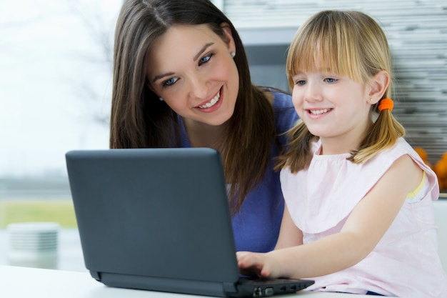 Mother and daughter using laptop in the kitchen