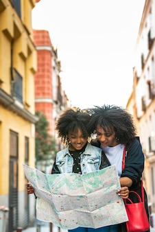 Mother and daughter using a map in the street