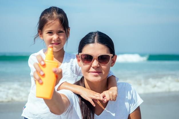 Mother and daughter using sunscreen on the beach