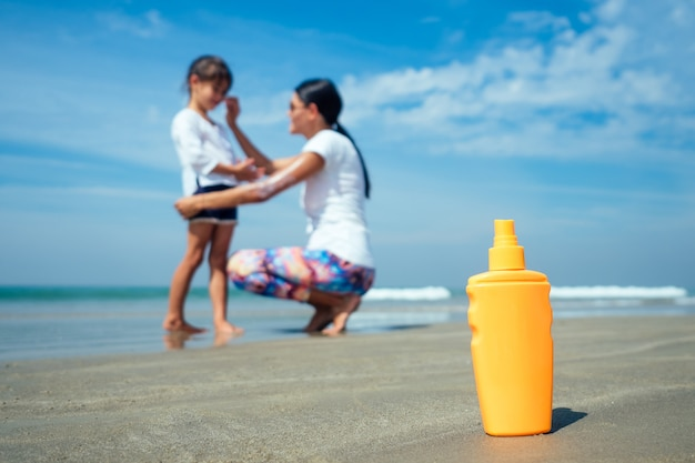 Mother and daughter using sunscreen on the beach.