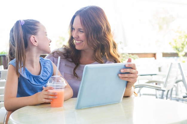 Mother and daughter using tablet at cafe terrace