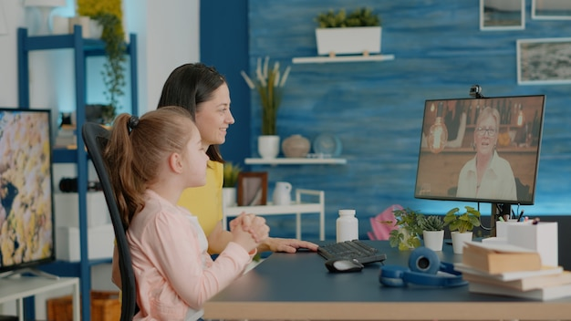 Mother and daughter using video call for chat with grandmother