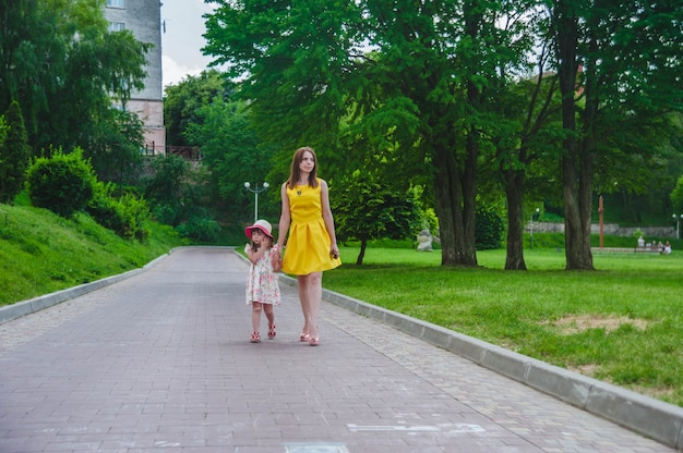 Mother and daughter walking on an asphalted road