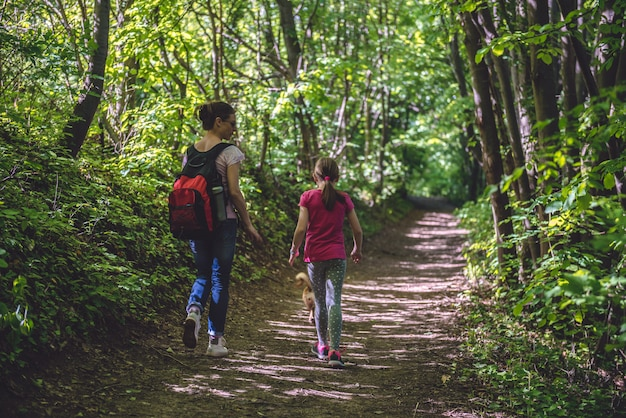 Mother and daughter walking on path in woods