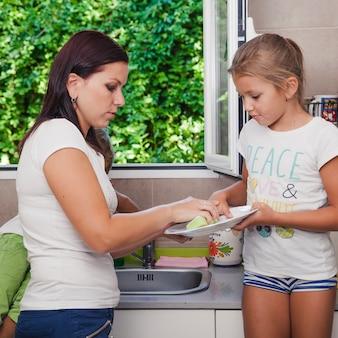Madre e figlia lavare piatto in piedi