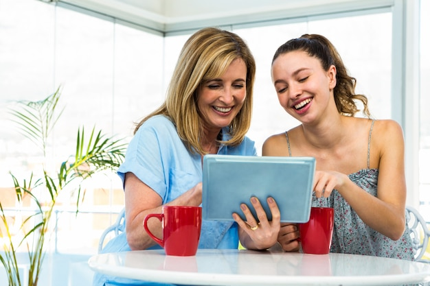 Mother and daughter watch tablet in the kitchen