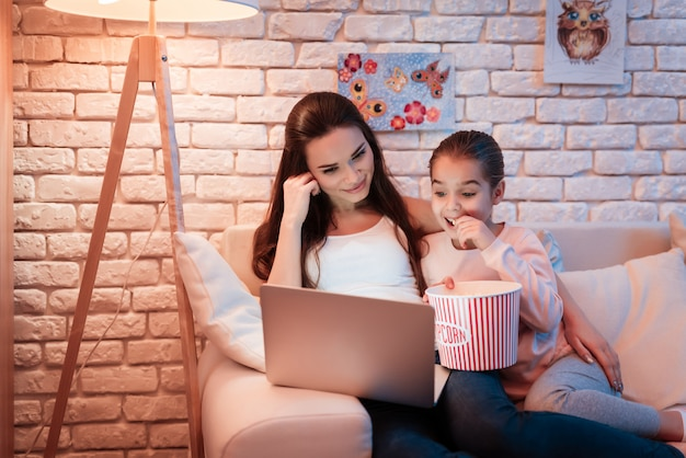 Mother and daughter watching movies and eating popcorn.