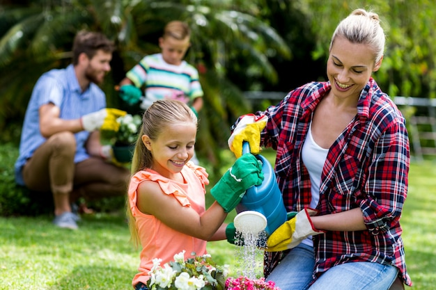 Mother and daughter watering flowers in yard