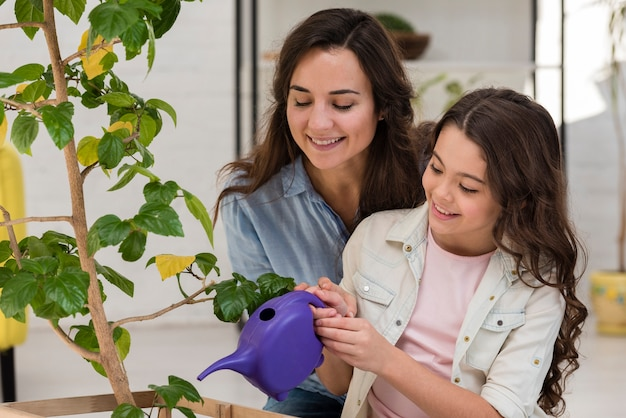 Mother and daughter watering the plant together