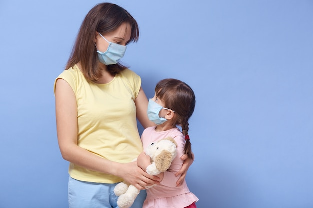 Mother and daughter wearing medical masks, hugging each other