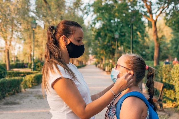 Mother and daughter wearing together masks on her faces.