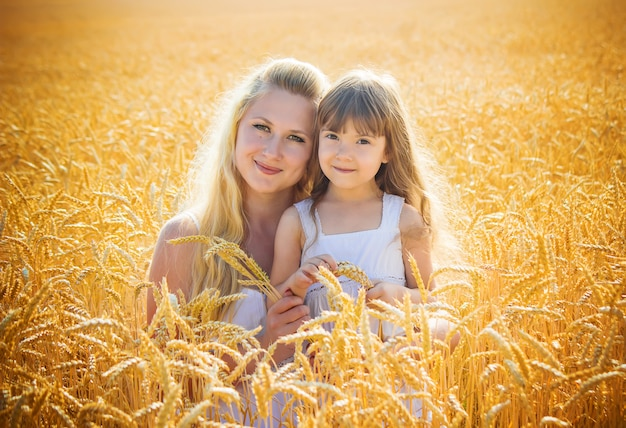 Mother and daughter in a wheat field. selective focus.